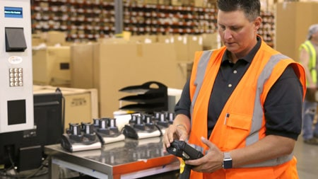 Distribution center Supervisor looking at barcode scanner